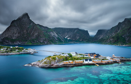turquise: Mount Olstind above the yellow cabins and turquise waters of Sakrisoy fishing village on Lofoten islands in Norway at evening blue hour. Long exposure. Stock Photo