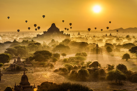 history background: Scenic sunrise with many hot air balloons above Bagan in Myanmar. Bagan is an ancient city with thousands of historic buddhist temples and stupas.