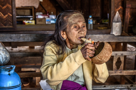 cheroot: BAGAN, MYANMAR - JANUARY 24, 2016 :  Old woman lights a cheroot cigar