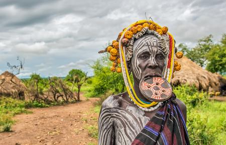 identidad cultural: Valle del Omo, Etiop�a - 7 de mayo, 2015: Mujer de la tribu Mursi africano con un plato grande de labios en su pueblo.