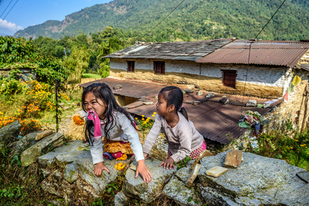 pokhara: POKHARA, NEPAL - OCTOBER 26, 2015 : Two nepalese girls play in the garden of their home