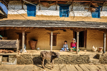 porch scene: DHAMPUS, NEPAL - OCTOBER 27, 2015 : Nepalese farmer woman with her son in the backyard of her farm house