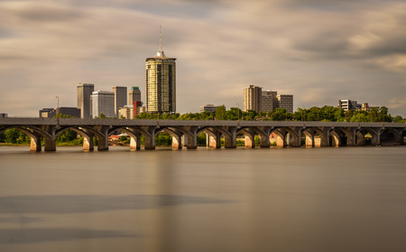 Sunset skyline of Tulsa, Oklahoma with Arkansas river in the foreground. Long exposure.