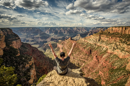 Grand Canyon and a happy hiker on the rim with arms raised up. Winner, success and achievement  concept in nature.
