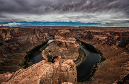 Horseshoe Bend, Colorado river and a hiker sitting at the edge and enjoying the panoramic view.