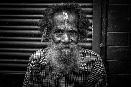 THAMEL, KATHMANDU, NEPAL - OCTOBER 28, 2015 :  Black and white portrait of an old man sitting in the street of Kathmandu Editorial