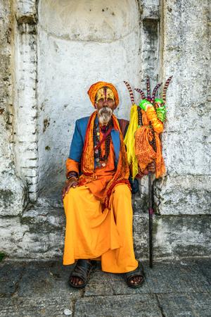 KATHMANDU, NEPAL - OCTOBER 21, 2015 : Wandering  Shaiva sadhu (holy man) with traditional face painting in ancient Pashupatinath Temple