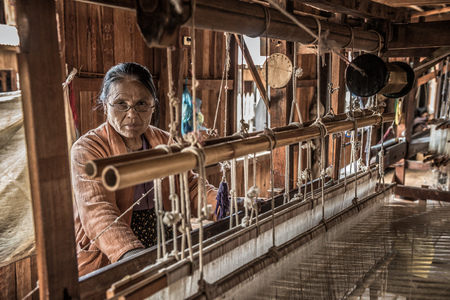INLE LAKE, MYANMAR - JANUARY 26, 2016 :  Woman worker weaves fabric in a weaving factory on Inle Lake.