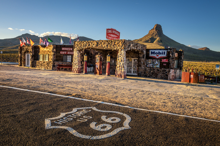 rebuilt: COOL SPRINGS, ARIZONA, USA - MAY 19, 2016: Rebuilt Cool Springs station in the Mojave desert on historic route 66 with the route 66 asphalt sign in front.