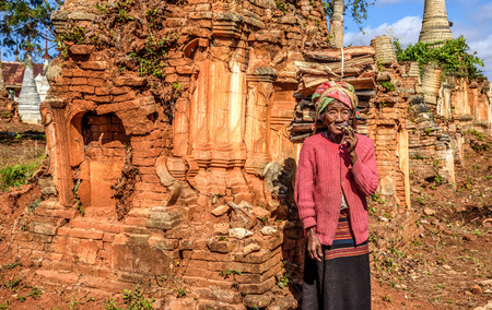 cheroot: AVA, MYANMAR - JANUARY 27, 2016 : old wrinkled woman smokes  a cheroot cigar around ruined temples in the ancient city  of Ava, also called Inwa Editorial