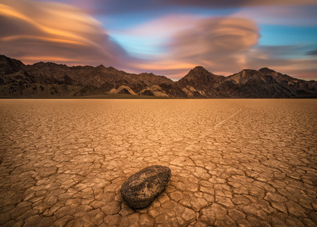 Sailing stone  on the The Racetrack Playa  in Death Valley National Park at sunset. The Racetrack Playa is a scenic dry lake with moving stones that inscribe linear imprints. Long exposure.