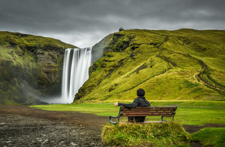 Hiker sits on a bench and looks at the famous Skogafoss waterfall in southern Iceland Stock Photo