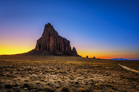 Sunset above Shiprock. Shiprock is a great volcanic rock mountain rising high above the high-desert plain of the Navajo Nation in New Mexico, USA Standard-Bild