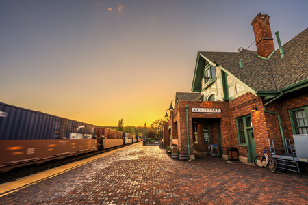 flagstaff: FLAGSTAFF, ARIZONA, USA - MAY 16, 2016 : Amtrak Train going through the historic train station in Flagstaff at sunset. This station is located on the historic Route 66. Editorial