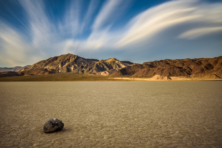 Sailing stone  on the The Racetrack Playa  in Death Valley National Park during golden hour. The Racetrack Playa is a scenic dry lake with moving stones that inscribe linear imprints. Long exposure. Stock Photo