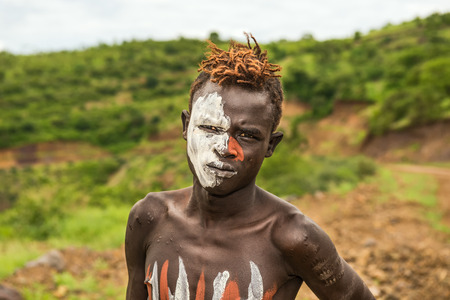 ethiopian ethnicity: OMO VALLEY, ETHIOPIA - MAY 7, 2015 : Young boy from the African tribe Mursi with traditionally painted face in Mago National Park, Ethiopia. Editorial
