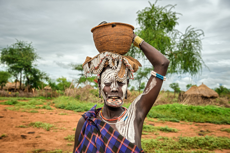 OMO VALLEY, ETHIOPIA - MAY 7, 2015 : Woman from the african tribe Mursi with big lip plate and with a basket on her head Editorial