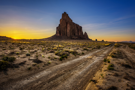 Sunset above Shiprock. Shiprock is a great volcanic rock mountain rising high above the high-desert plain of the Navajo Nation in New Mexico, USA Stock Photo