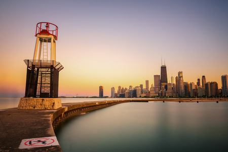 CHICAGO, ILLINOIS, USA - MAY 30, 2016 : Chicago skyline across Lake Michigan at sunset viewed from North Avenue Beach with a lighthouse in foreground. Long exposure.