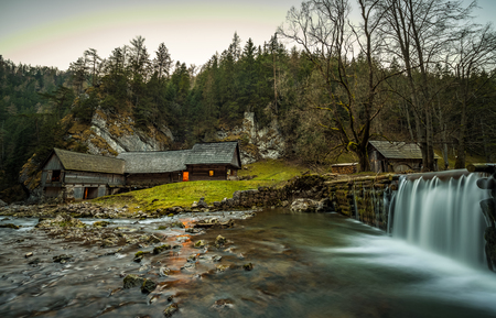 Old wooden water mill at National Nature Reserve Kvacianska dolina in Slovakia after sunset.  It has been restored and serves as a museum. Long exposure. Stock Photo