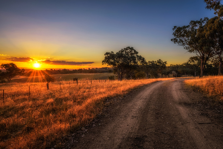 Scenic countryside landscape with rural dirt road at sunset in Australia