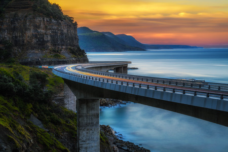 Sunset over the Sea cliff bridge along Australian Pacific ocean coast with lights of passing cars near Sydney, Australia. Long exposure.