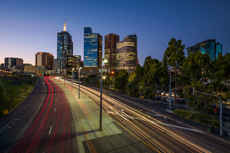 Light trails of traffic with illuminated skyscrapers of Melbourne downtown after sunset in Victoria, Australia