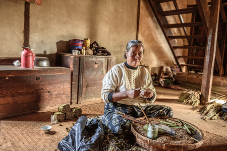 PINDAYA, MYANMAR - JANUARY 25, 2016 : Old woman working in her home