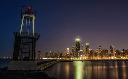CHICAGO, ILLINOIS, USA - MAY 30, 2016 : Chicago skyline across Lake Michigan at night viewed from North Avenue Beach with a lighthouse in foreground. Long exposure.