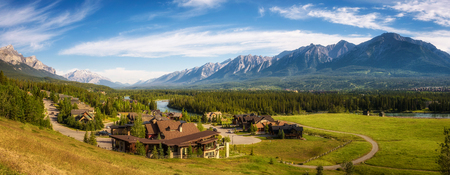 canmore: CANMORE, CANADA - JUNE 26, 2017 : Canmore in the Rocky Mountains with mountain peaks in background. Canmore is located in the Bow Valley near Banff National Park and is a popular tourist destination.
