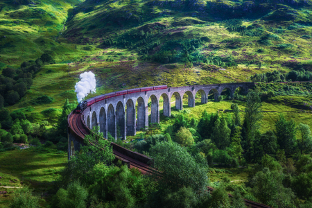 Glenfinnan Railway Viaduct in Scotland with the Jacobite steam train passing over. Artistic vintage style processing. Zdjęcie Seryjne - 82681763