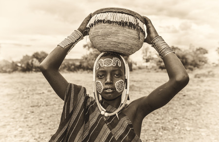 ethiopian ethnicity: OMO VALLEY, ETHIOPIA - MAY 7, 2015 : Young boy from the African tribe Mursi with traditional jewelry in Mago National Park, Ethiopia. Vintage black and white processed.