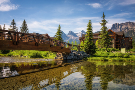 canmore: CANMORE, CANADA - JUNE 26, 2017 : Hotels in Canmore with mountain peaks in the background. Canmore is located in the Bow Valley near Banff National Park and is a popular tourist destination.