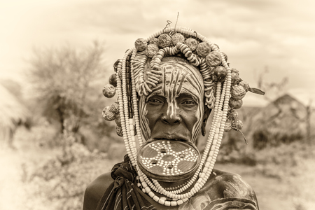 ethiopian ethnicity: OMO VALLEY, ETHIOPIA - MAY 7, 2015 : Woman from the african tribe Mursi with big lip plate in her village. Vintage black and white processed. Editorial
