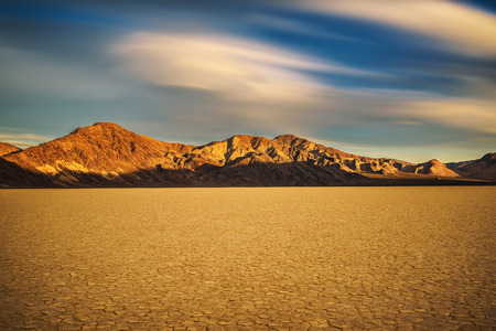 Scenic sunset at Racetrack Playa  in Death Valley National Park. The Racetrack Playa is a scenic dry lake with moving stones that inscribe linear imprints. Long exposure.