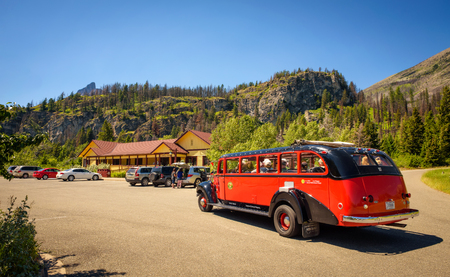 saint: GLACIER NATIONAL PARK, MONTANA, USA - JULY 5, 2017 : : Iconic  Red Bus with tourists at the Rising Sun Motor Inn  near Saint Mary Lake in Glacier National Park.