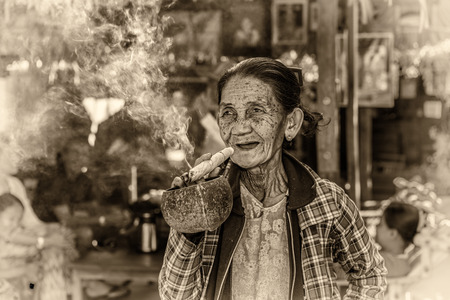 cheroot: BAGAN, MYANMAR - JANUARY 24, 2016 : Happy and old wrinkled woman smokes  a big cheroot cigar in public. Vintage black and white processed.