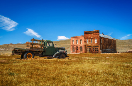 Car wreck and old buildings in Bodie ghost town, California. Bodie is a historic state park from a gold rush era  in the Bodie Hills east of the Sierra Nevada