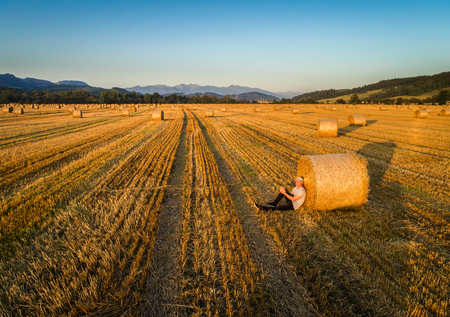 hayroll: Young man enjoys sunset at a farm field with hay bales