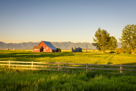 Summer sunset with a red barn in rural Montana and Rocky Mountains