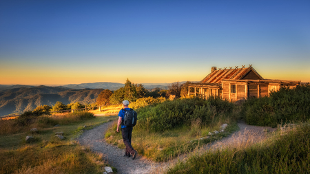 Young hiker with backpack approaching a hut in Australia Stock Photo