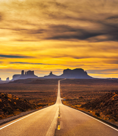 Desert road leading to Monument Valley at sunset
