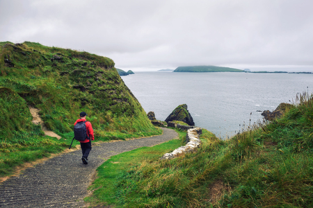 Young man walks along pathway surrounded by irish landscape