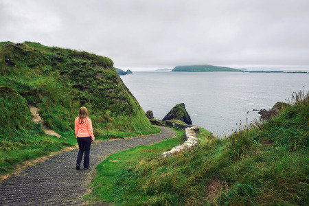 Young woman walks along pathway surrounded by irish landscape