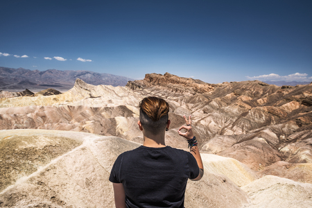 Death Valley and a visitor doing okay gesture with his hand Standard-Bild - 127561307