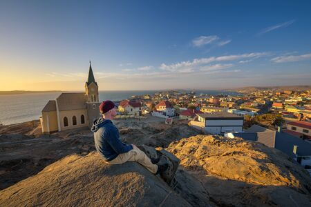 Tourist on top of a hill enjoys the view of Luderitz in Namibia at sunset
