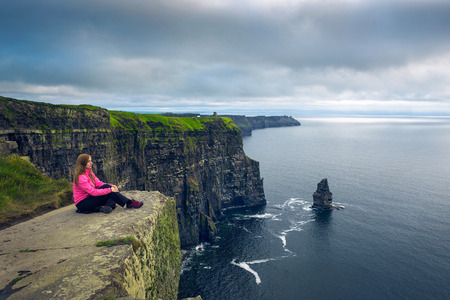 Young woman sitting at the cliffs of Moher Standard-Bild - 127115100