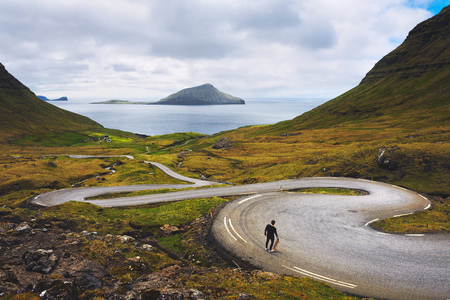 Young skater with his skateboard looks at the beatiful scenery of Faroe Islands Standard-Bild - 127115038