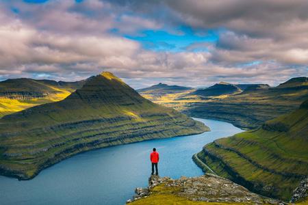 Hiker enjoys views over fjords from a mountain near Funningur on Faroe Islands Standard-Bild - 127115067