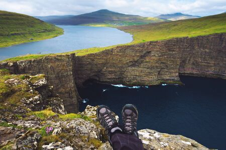 Legs of hiker sitting on top of a cliff over lake Sorvagsvatn on Faroe Islands Standard-Bild - 127115072